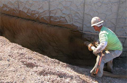A concrete construction worker hold a shotcrete pipe applying concrete to a pool base.