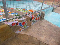Hand painted flowers on a concrete overlay in a sea blue guide people to the front of a building in Texas