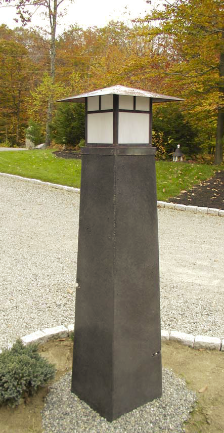 Concrete lighthouse serves as the road marker and porch light for this house.