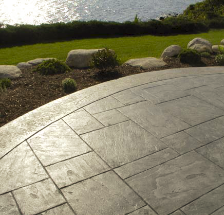 Stamped concrete patio overlooking water.