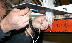 Fiber Optic Light Effects - Fibers are fed through a metal plate in order according to the illumination program. The ends are cut with a hot wire for a clean edge that will not pull out of the plate.