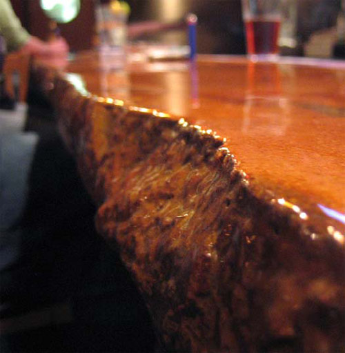 """This 26-foot-long cast-in-place bar looked like a """"Flintstone bar"""" at first, according to artisan Michael Crane. It came out with broken edges and a pale orange tone that wasn't quite right. He ground it, leaving color in recessed areas, and finished with a two-part epoxy."""
