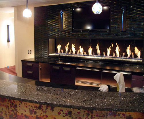 A concrete countertop bar top in front of a fire feature backdrop