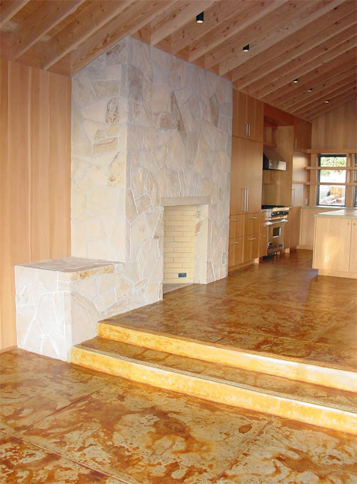 A floor to ceiling fireplace with faux stones that butts up against an acid stained floor.