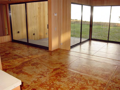 Sliding doors lead from the stained concrete floor out to a grassy space.