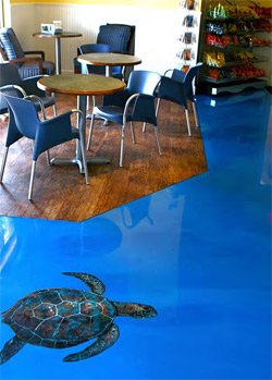 A sea turtle was painted on this concrete floor that has been covered with blue epoxy.