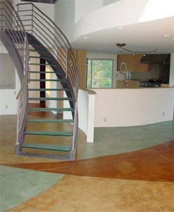 This living room space equipped with open stairs to the second floor shows a concrete floor thath as been stained in three colors, green, tan and brown