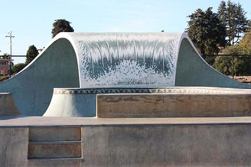 A skatepark that has been customized with a wave-like full pipe made of concrete.