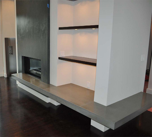 A modern concrete fireplace with the hearth continuing throughout the space under the bookcase and around the corner.
