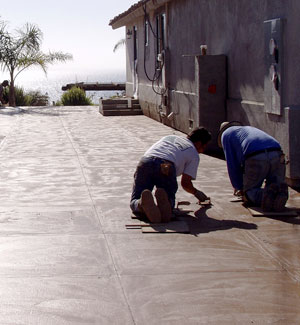 Two contractors using a saw-cut joint tool on a large concrete patio