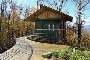 The entrance to the concrete treehouse comes by way of an elevated concrete pathway from the main house.
