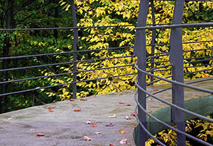 The elevated pathway that leads to the concrete treehouse is lined with metal handrails.