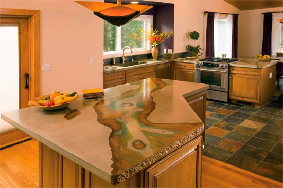 Concrete countertop on an island in a kitchen brings in a natural river aspect in colors and design.
