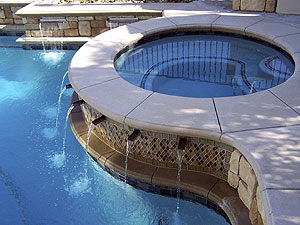 Hot tub next to a pool and a water feature keeps the water circulating.