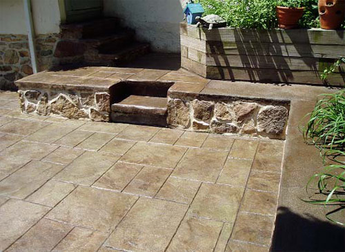 Color hardened concrete steps in dark brown. Patio stamped tile pattern colored tan.