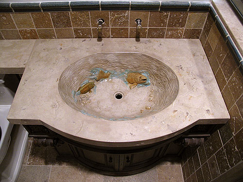 A look at a custom concrete sink that has a fish carved in it.