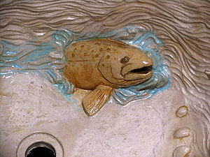 An upclose view of the fish that was carved into this concrete sink
