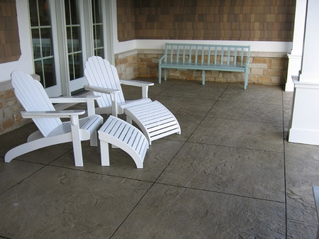 Adirondack chairs sitting on a stamped concrete porch.