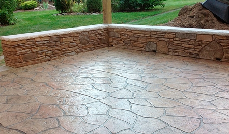 Stamped concrete patio with sitting wall.