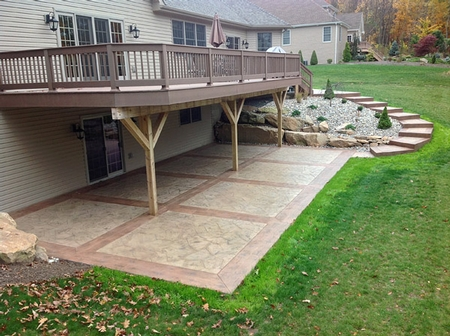 Concrete patio with stamped and stained concrete and red borders.