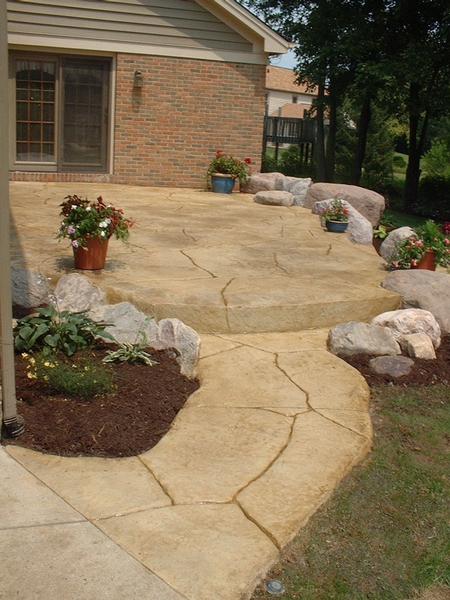 Natural looking concrete porch that looks like stone laid by hand leading up to a front door.