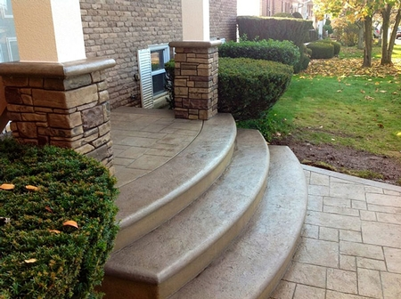 Radial steps stained in a brown color with stamped concrete leading to the first step.