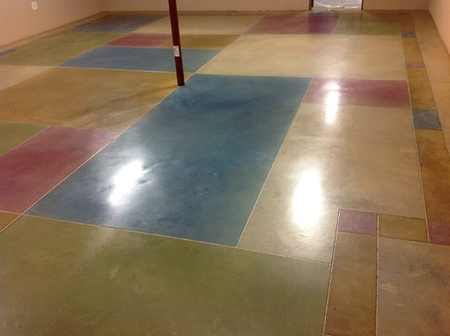 Dyed concrete floor with multiple color blocks in reds, greens blues and tans.