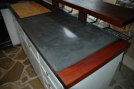 dark gray concrete countertop with a wood border.