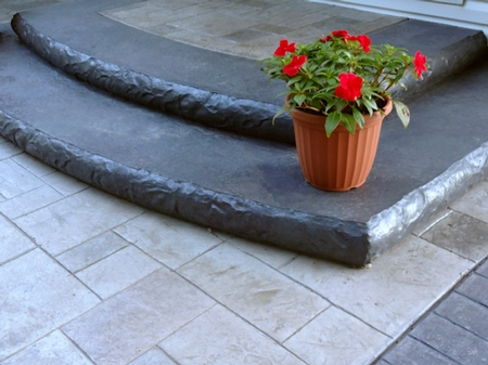 Gray concrete steps with a flower pot sitting on the edge.