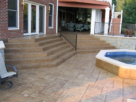 Concrete stairs leading to a large concrete patio complete with a water feature.
