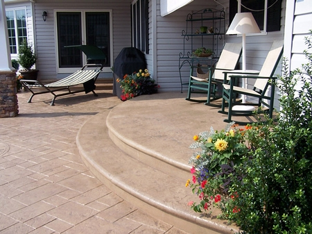 Large concrete patio with two curved steps leading into the home.