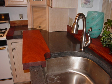 dark gray concrete countertop with a stainless steel sink in the kitchen