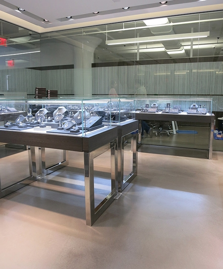 A high end jewelry store with concrete floors and countertops.