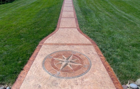 A long concrete pathway with a stained compass rose making its way through green grass.