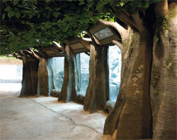 Zoo hallway lined with concrete tree trunks and a large green canopy.