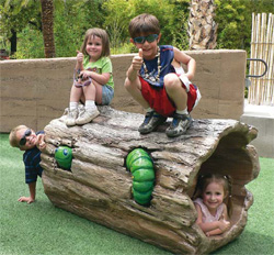 Hollow log made of concrete with four children and a green concrete worm playing.