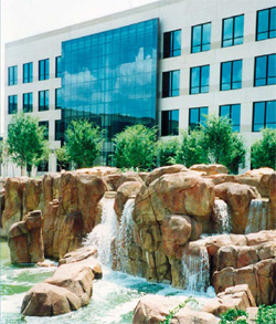 Large water feature made of concrete in front of a glass office building.