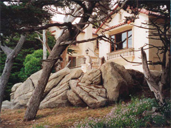 Pile of large boulders in front of a home in a rustic setting made of concrete.