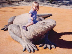 Little girl sitting on top of a large concrete lizard.