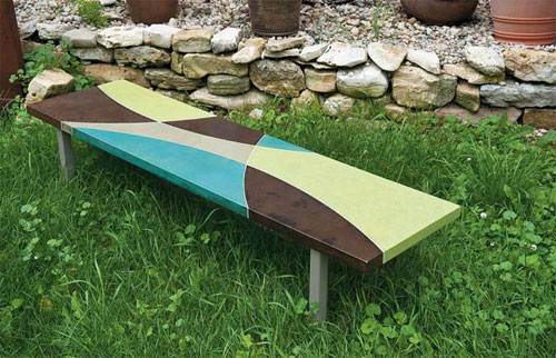 A green, teal and brown concrete bench on green grass.