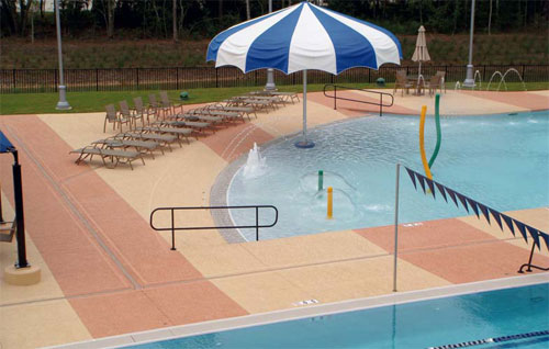 A concrete pool deck resurfaced with light brown and red stripes.