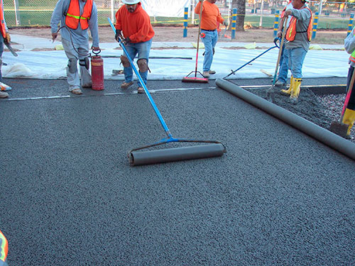 Workers for Arizona-based Progressive Hardscapes install the Drainscape pervious concrete system. The lack of thermal mass in pervious concrete allows it to cool down more quickly at night.