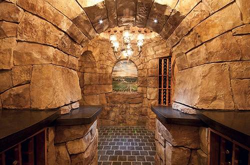 A look at an arch in a wine cellar created with faux rocks.