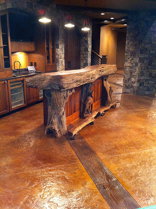 A bluestone-stamped field trimmed with richly stained faux beams, this technique is perfectly suited for any room with an upscale rustic theme.