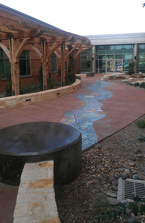 In addition to a durable surface, the hospital wanted to feature a river theme representing the San Antonio River and utilize different textures and colors covering almost 26,000 square feet of concrete.