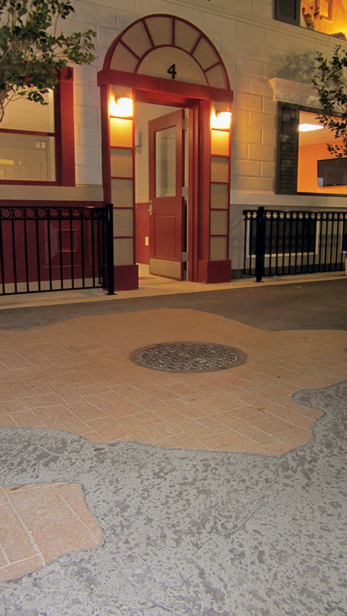 Stampable overlay carved to obtain the look of asphalt with concrete and broken edged bricks.