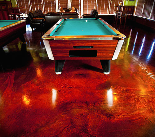 Acid stained concrete under a pool table gives the space an old-timey feel.