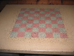Square light tan precast concrete table with a checker board cast into the center