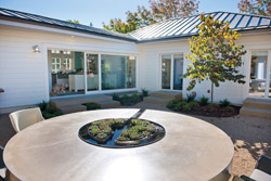 Copper colored round precast concrete outdoor table with a mini garden in the center circle.