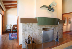Green fireplace mantel cast out of concrete in a stately living room.